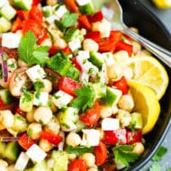 Mediterranean Chickpea Salad in a black bowl with a spoon.