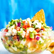 Gluten-free Mexican shrimp ceviche in a glass bowl surrounded by tortilla chips.