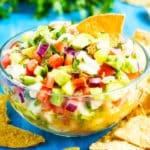 A bowl filled with a shrimp ceviche recipe and tortilla chips.