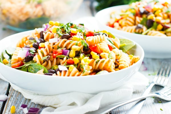 Gluten-free ranch pasta salad recipe in a white bowl with two forks.