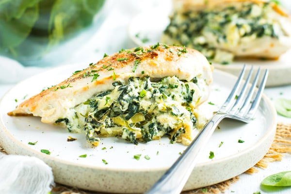 Spinach stuffed chicken breasts full of spinach and artichoke filling with a sprinkle of parsley on a white plate with a fork.