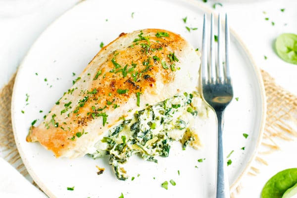 Stuffed chicken breast recipe with spinach and artichoke on a white plate with a fork.