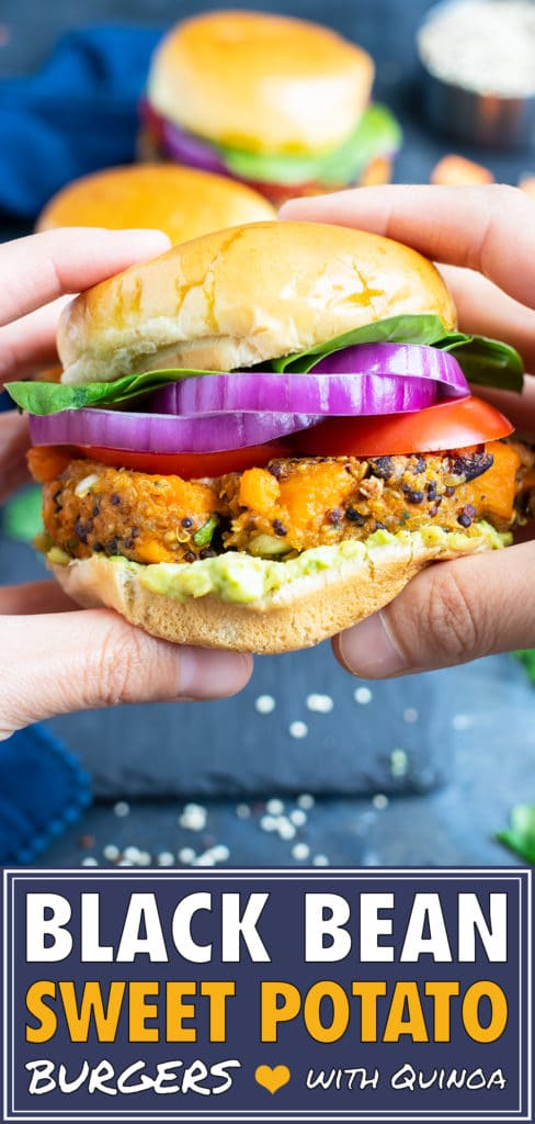 Two hands holding a healthy black bean quinoa burger with sweet potatoes, red onion, and avocado.