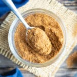 Homemade taco seasoning recipe in a glass container with a silver spoon scooping some out.