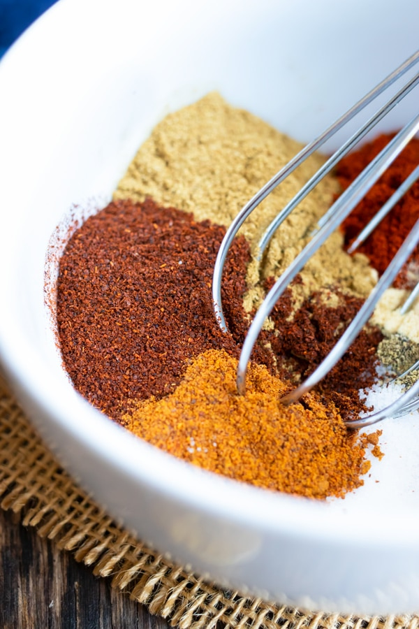 A white bowl full of spices for a DIY taco seasoning mix with a whisk.