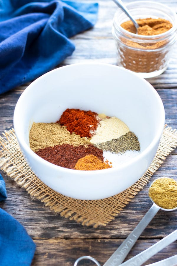 Multiple Mexican spices in a white bowl to make a gluten-free, Paleo, and Whole30 taco seasoning recipe.