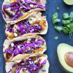 Four blackened fish tacos with avocado sauce and cabbage on a black plate.