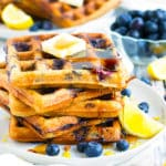 A pile Paleo Lemon Blueberry Waffles on a plate with a white napkin.