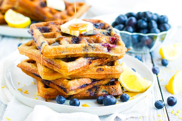 A stack of paleo waffles with blueberries on a plate.