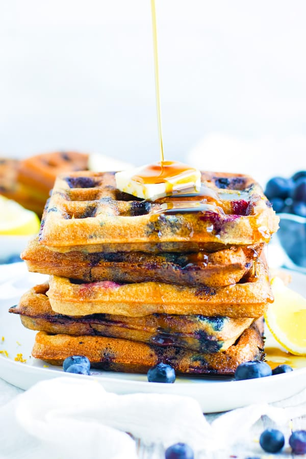 Syrup being poured on this blueberry waffle recipe.