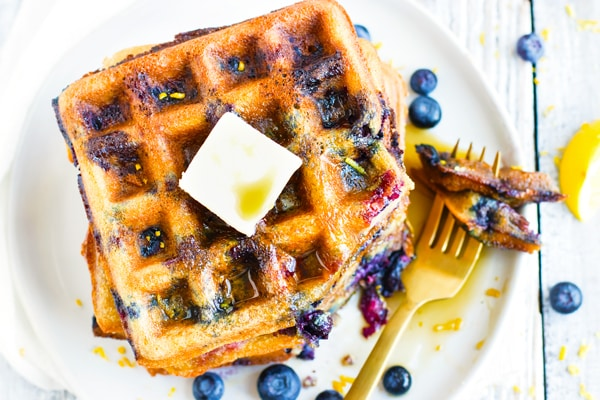Paleo Lemon Blueberry Waffles on a white plate with a fork.