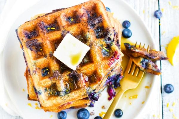 Paleo Lemon Blueberry Waffles on a white plate with a fork.