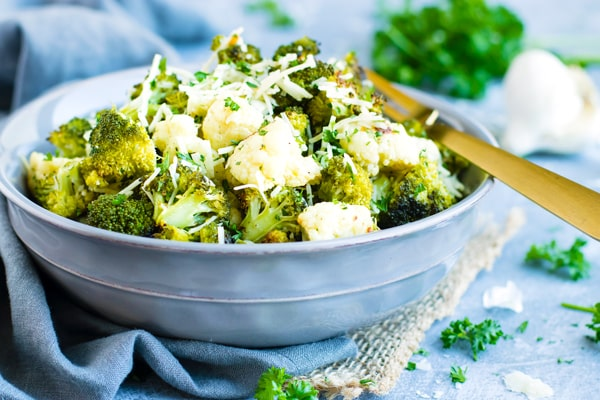 Gluten-free roasted broccoli cauliflower in a blue bowl with a fork.