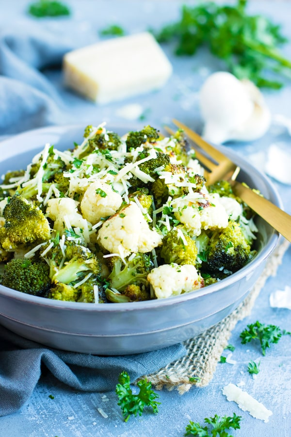Parmesan Garlic Roasted Broccoli and Cauliflower in a bowl on a blue napkin.