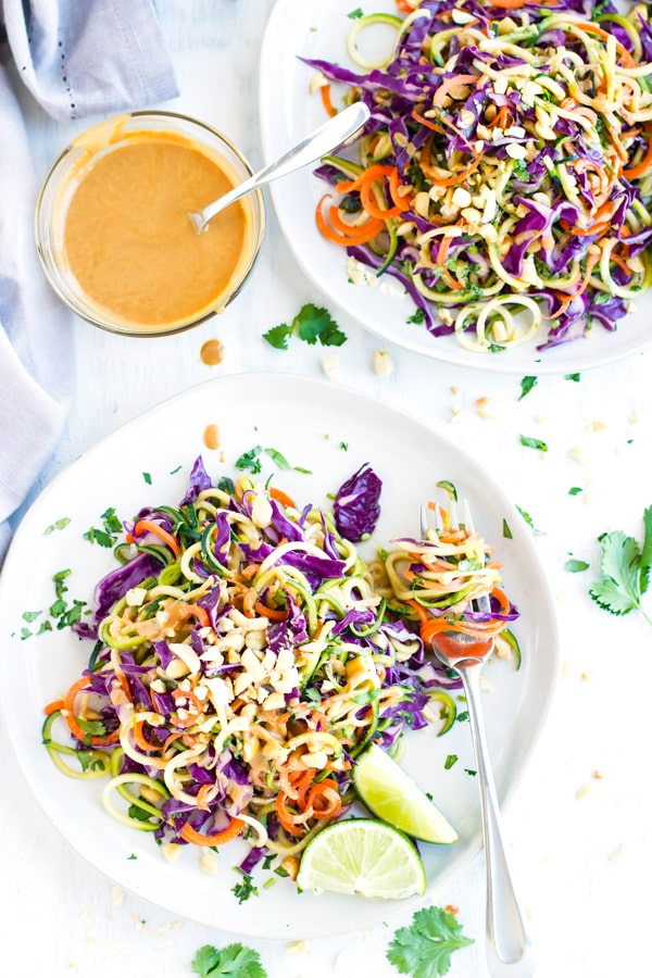 Two plates of cold zucchini noodle salad with sauce in between.