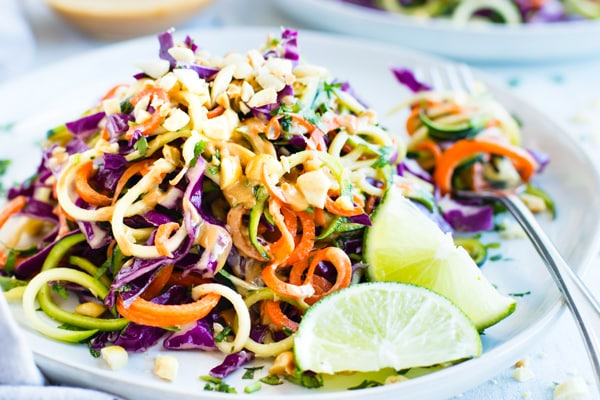 Easy zucchini noodle salad recipe on plate with limes for lunch.