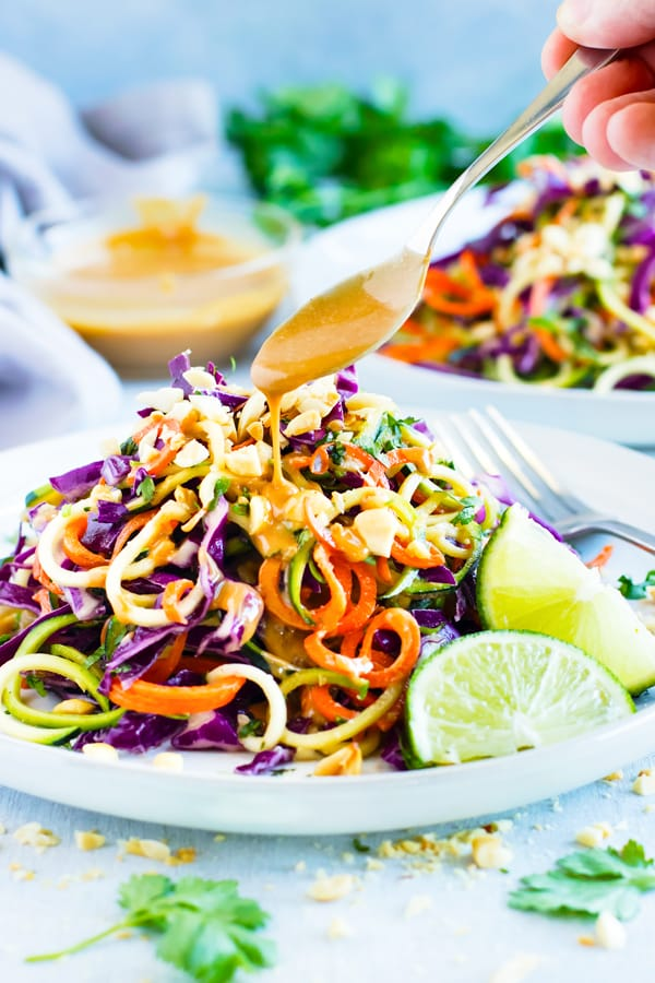 Gluten-free Thai Zucchini Noodle Salad with dressing drizzled on the top.