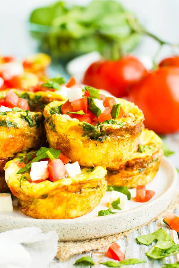 Low-carb egg muffins stacked on a plate with tomatoes in the background.