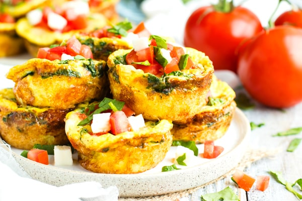 Healthy egg muffins in a pile on a plate topped with chopped tomatoes.