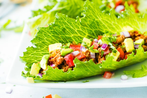 A single Ground Turkey Taco Lettuce Wrap recipe on a white plate.