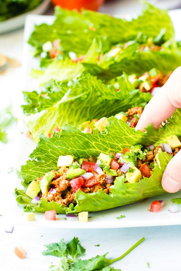 A hand picking up turkey taco lettuce wraps on a white plate.