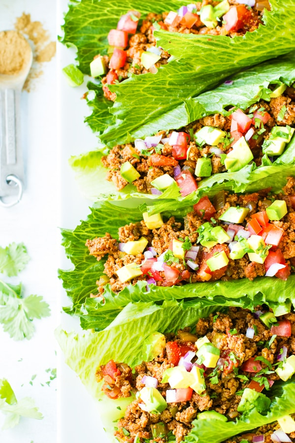 A row of taco lettuce wraps on a white plate.