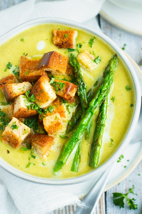 An overhead picture of Creamy and Healthy Asparagus Soup with bread cubes.