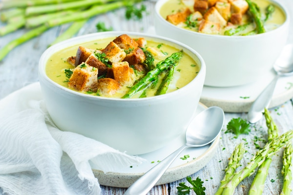 A white bowl full of a creamy asparagus soup recipe for lunch.