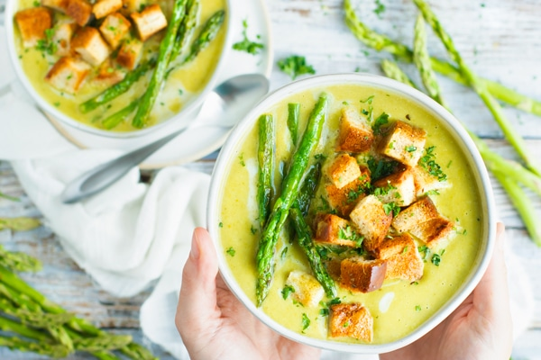 A hand holding a bowl of vegan asparagus soup with a white napkin.