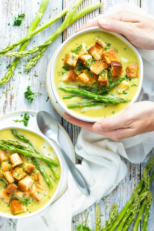 A hand holding a white bowl of gluten-free cream of asparagus soup on a table.