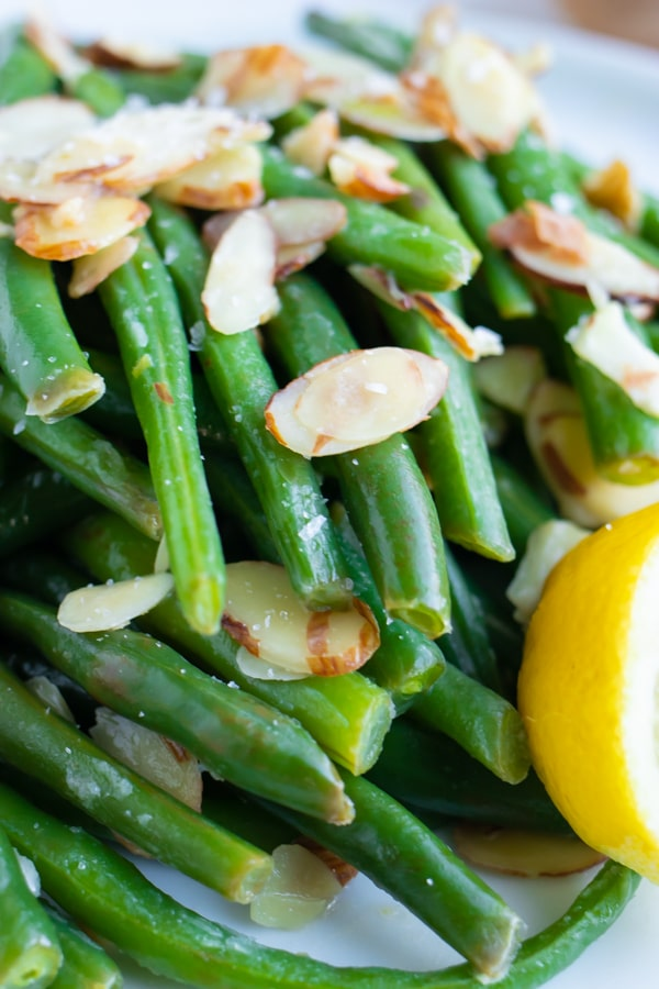 Sliced almonds on top of boiled and blanched green beans with lemon juice.