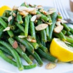 A serving of cooked green beans with lemon zest and toasted almonds on top.