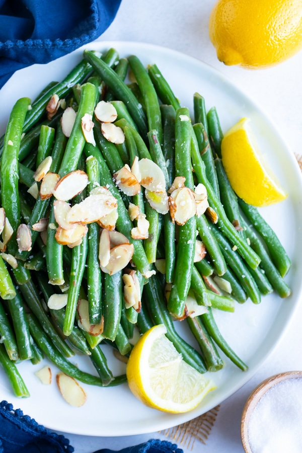 A plate full of green beans almondine with lemon wedges and a fork.