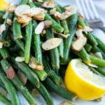 A white plate with a green beans almondine recipe with a fresh lemon slice.