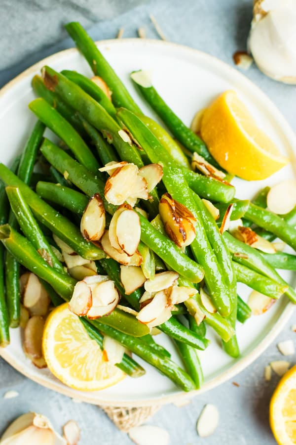 String beans almondine on a white plate topped with sliced almonds and garnished with two lemon slices and garlic.