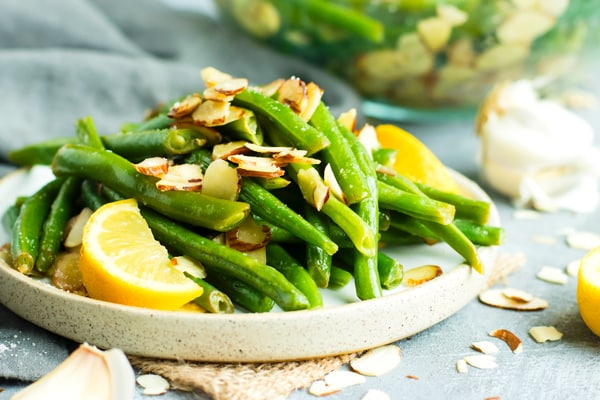 Green bean almondine recipe on a white plate with a lemon wedge and sprinkled with sliced almonds.