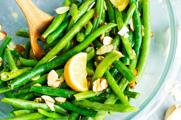 Green beans almondine with slivered almonds and lemon wedges in a clear bowl with a wooden spoon.