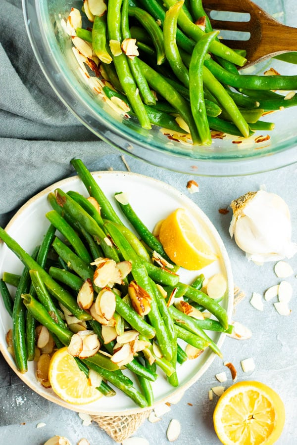 A white plate with a serving of green beans almondine that is topped with sliced almonds and garlic.
