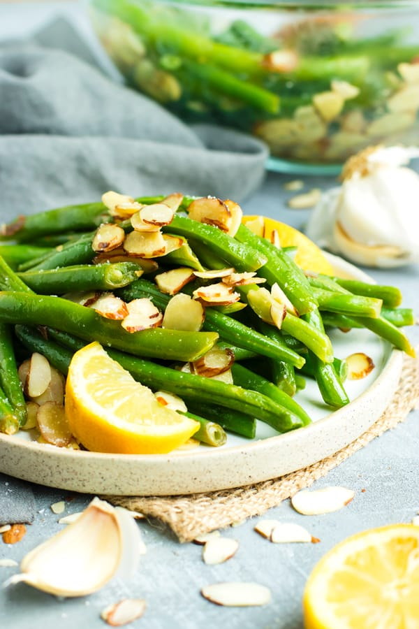 A serving of green beans almondine on a white plate with sliced almonds and a sprinkle of salt