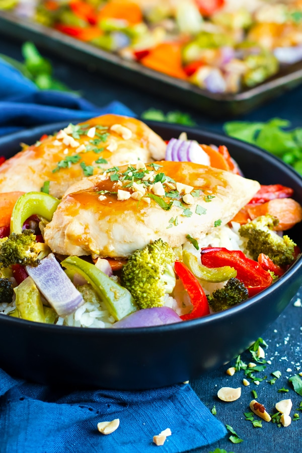 Sheet pan chicken with a Thai peanut sauce recipe in a black bowl.