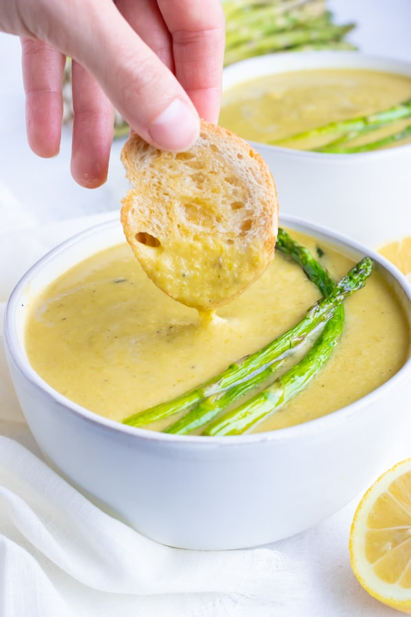 A toasted baguette being dipped into a bowl full of creamy asparagus soup.