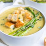 A white serving bowl full of a creamy asparagus soup recipe with roasted asparagus spears and homemade croutons.