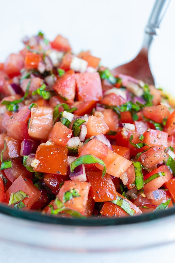 Fresh diced tomatoes, basil, garlic, and red onion being tossed together in a bowl to make bruschetta.