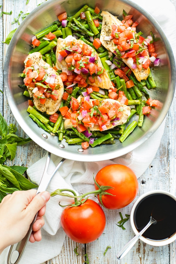 Beautiful overhead picture of Skillet Bruschetta Chicken and Asparagus in a silver skillet with whole tomatoes.