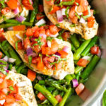An overhead picture of chicken and asparagus in a silver skillet with tomatoes.