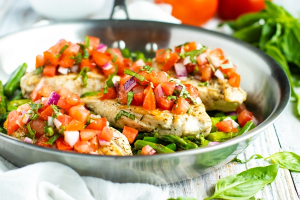 Healthy bruschetta chicken recipe in a silver skillet.