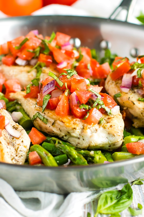 Gluten-free bruschetta chicken in a skillet with chopped tomatoes.
