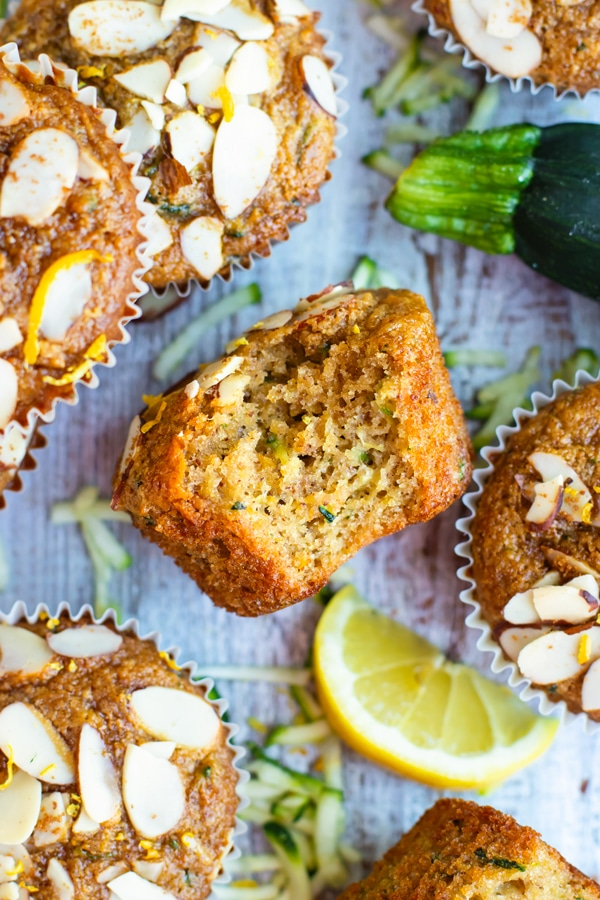 Gluten-free zucchini muffin with a bite inside surrounded by other muffins.
