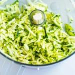 Shredded zucchini inside a food processor to make a zucchini muffin recipe.