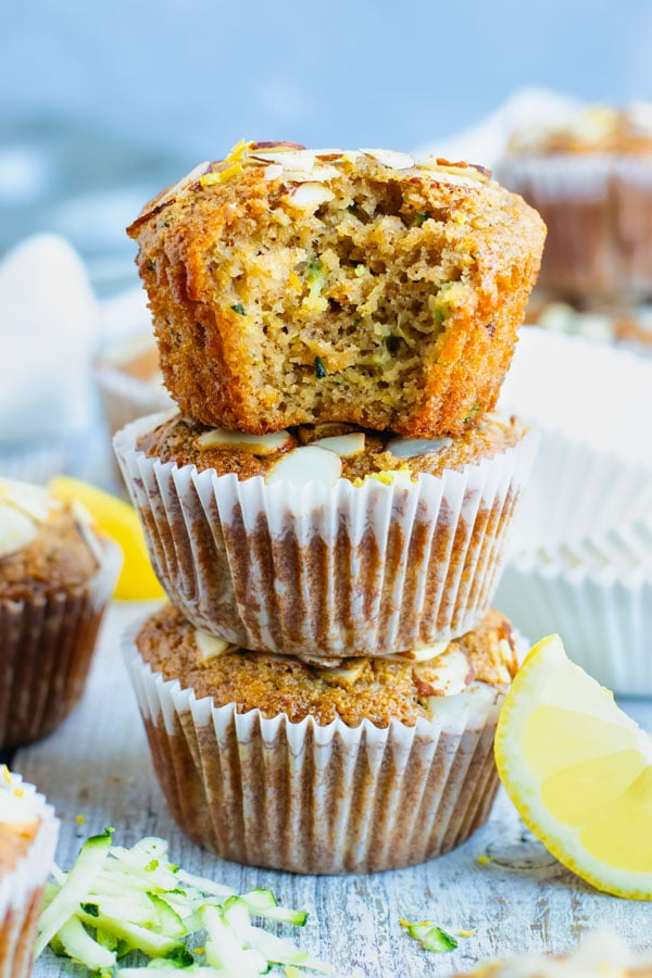 A pile of easy healthy zucchini muffins on a table with a lemon slice.